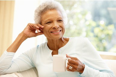 Black woman with coffee cup and white sweater