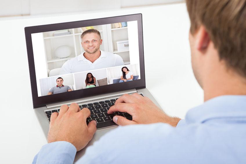 30580945 - rear view of businessman video conferencing on computer at desk in office