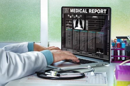 58852246 - physician in consultation with a medical record of a patient on the screen of the laptop / doctor consulting a medical history on a computer
