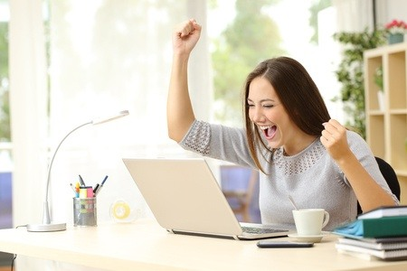 50532398 - euphoric winner watching a laptop on a desk winning at home